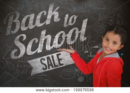 Portrait of smiling girl gesturing against white background against close-up of blackboard