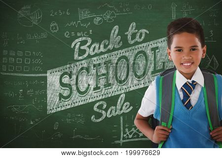 Portrait of schoolboy carrying schoolbag against white background against green background