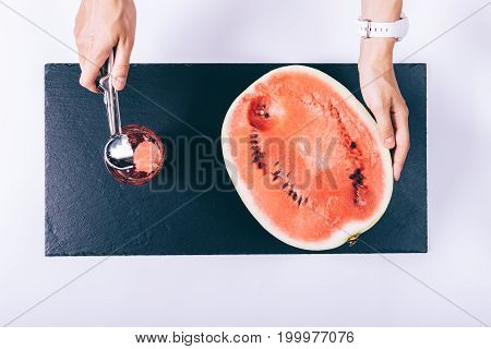Female Hands Cut A Watermelon With A Spoon And Put The Pieces In A Glass On A White Table
