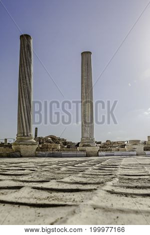 Doric white marble columns ruins from low angle with floor Caesarea national park