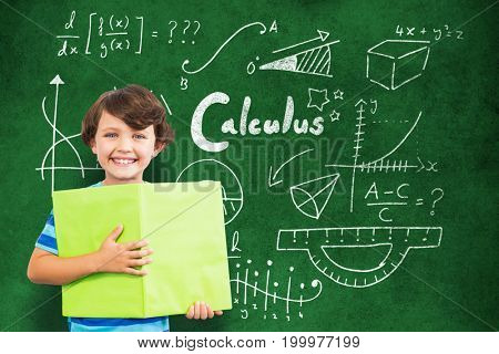 Portrait of smiling boy holding green book against close-up of blackboard