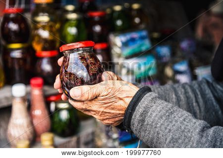 Wrinkled old female hands hold a jar with homemade jam made of cones in the mountains
