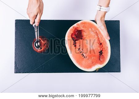 Women Hands Sliced Watermelon With A Spoon And Put The Pieces In A Glass On A White Table