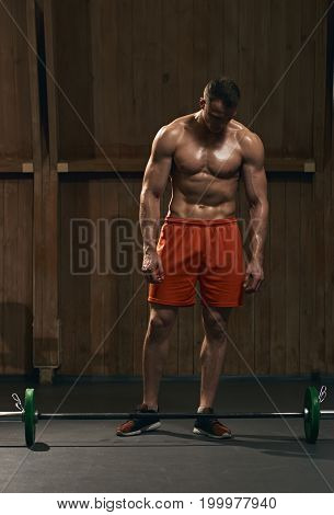 Healthy sporty man preparing for training and looking at barbell