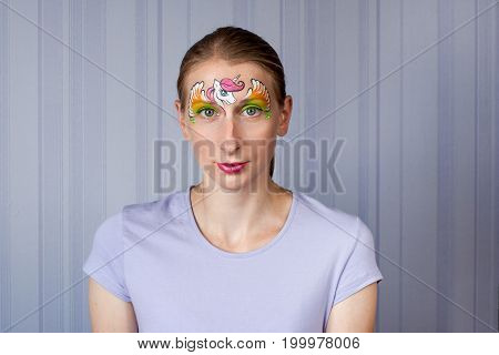 Young woman with face painting pony mask