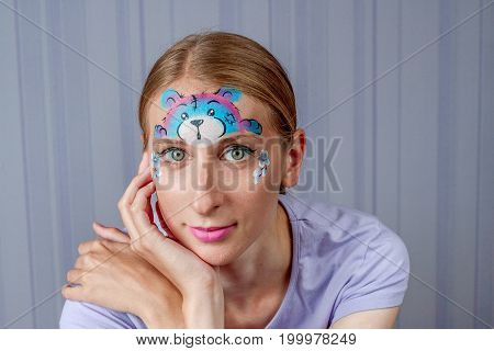 Young woman with face painting pink teddy bear mask