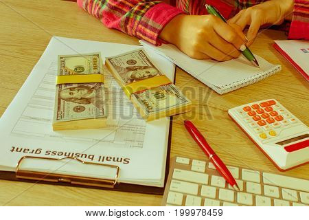 Young woman working in home sitting at desk using computer. Business grant and finances concept. Business executive woman at workplace - Retro color