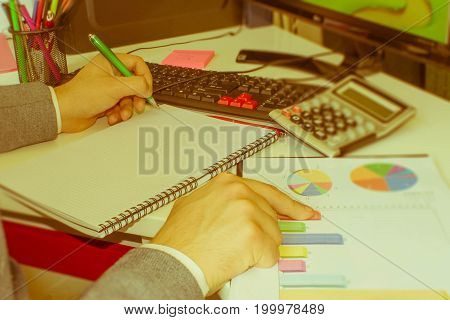 closeup pen on paperwork accounts with man use computer to save data in background. accounting concept. Man hand with pen calculator and computer on wooden table - Retro color