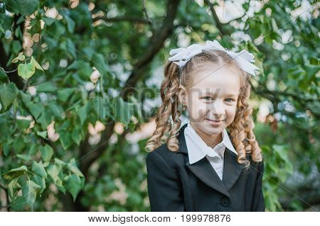 Portrait of a beautiful young school girl standingon the background autumn park. Farewell Bell. day of knowledge. beginning of the school year.