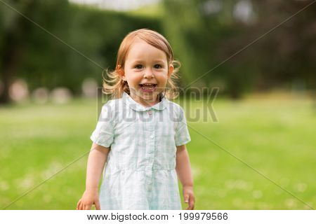 childhood, leisure and people concept - happy baby girl on green summer field