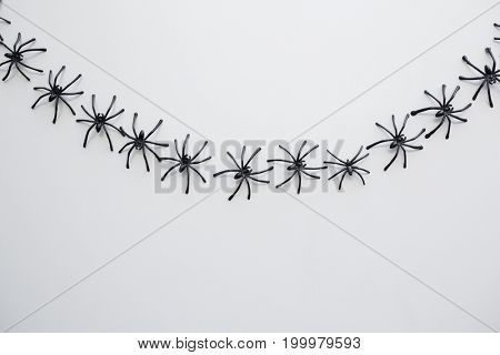 halloween, decoration and scary concept - black toy spiders chain over white background