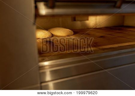 food, cooking and baking concept - yeast bread dough in oven at bakery kitchen