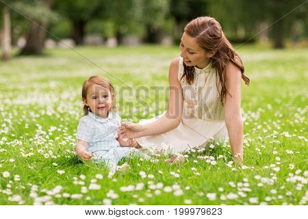 family, childhood and parenthood concept - happy mother with little baby girl at summer park