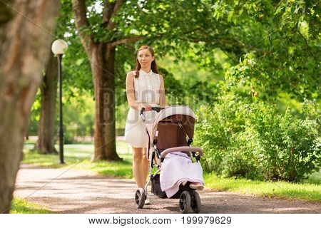 family, motherhood and people concept - happy mother with child sleeping in stroller walking at summer park