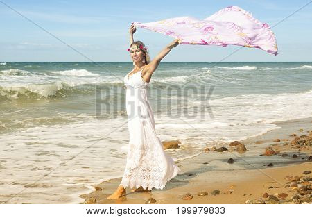 beautiful blond woman in white dress walking on the beach and holding a shawl in the wind