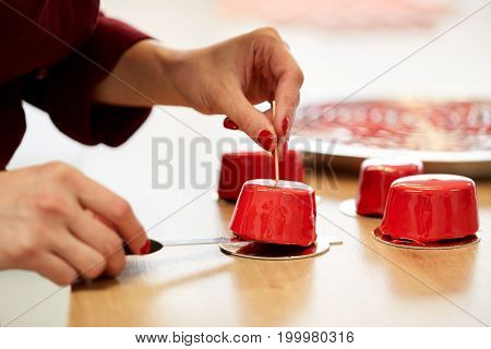cooking, baking and confectionery concept - chef serving mirror glaze cakes at pastry shop
