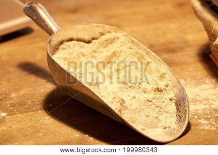 food, cooking and baking concept - flour in bakery scoop on wooden kitchen table