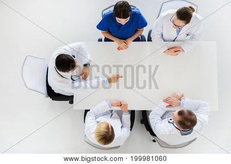medicine, healthcare and people concept - doctor showing something imaginary on table