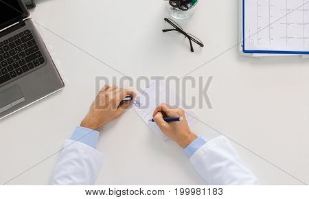 medicine, healthcare and people concept - doctor hands with prescription at table in clinic