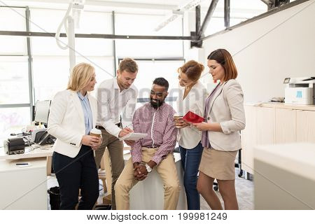 business, break, communication and people concept - happy creative team with notebooks drinking coffee and talking at office