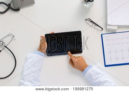 medicine, healthcare and people concept - doctor with tablet pc computer and cardiogram sitting at table in clinic