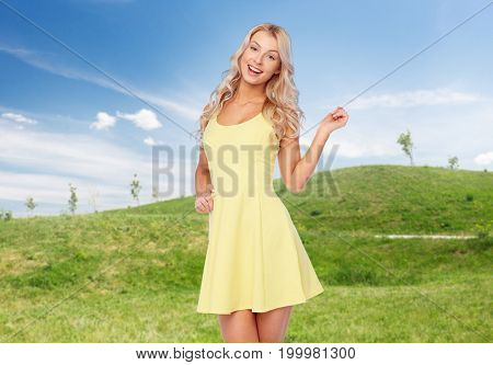 fashion, summer and people concept - happy smiling beautiful young woman posing in yellow dress over blue sky and green field background