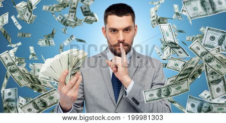 business, people and finances concept - businessman with bundle of american dollar cash money over blue background