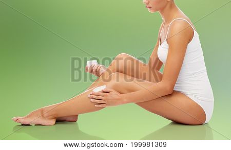 people, beauty, cosmetics, bodycare and skincare concept - beautiful woman applying moisturizing cream to her leg over green natural background