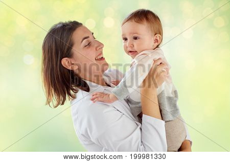 medicine, healthcare, pediatry and people concept - happy woman doctor or pediatrician holding baby over green lights background