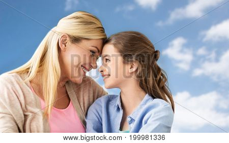 people and family concept - happy smiling girl with mother over blue sky and clouds background