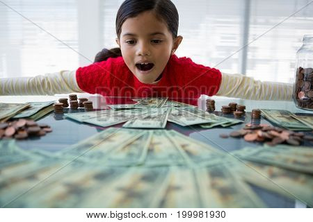 Girl with arms outstretched looking at currency at desk in office
