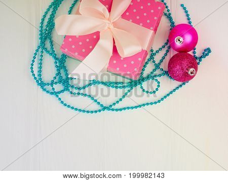 the gentle pink new Christmas gift with a nice ribbon, bowknot, white wood background, copy space for text, concept of the gift. holiday, gift, added a snow effect, with two Christmas ball. flatlay