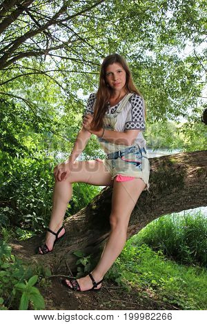 Young woman with summer sprouts and dungarees while fishing