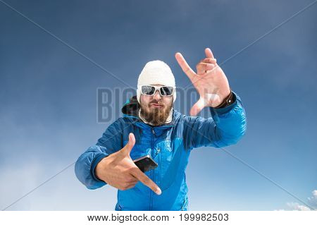 A portrait of a bearded traveler on the mountains in sunglasses and a hat dancing to the music on the phone and showing the gesture of the camera frame.