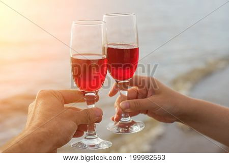 Two Red Wine Glasses In Couple Hands Silhouettes Against Sea Sunset.