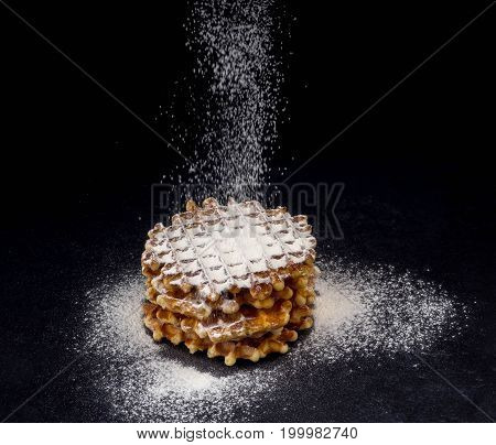 White plate with homemade Belgian waffles, on top of poured sifting of powdered sugar on black background, very tasty snack. sugar over old wooden table. Dark rustic style. copy space for text, stylish