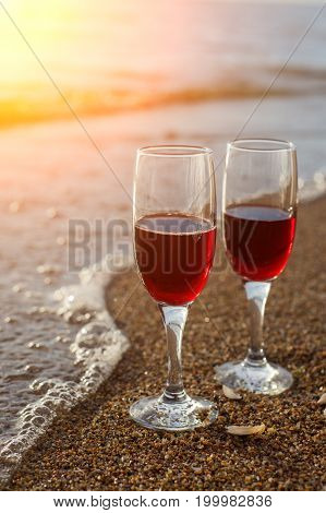 Two Red Wine Glasses In Front Of The Setting Sun.