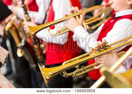 jazz band performance concept - orchestra of wind instruments during the variety show, selective focus on hands of musicians playing on trumpets and saxophones, closeup male in red concert costumes