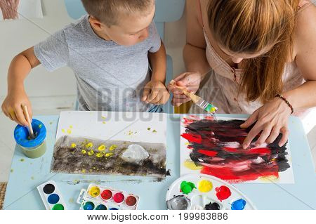 The child draws with his mother or teacher. view from above