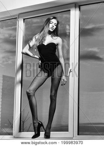 woman with long hair and legs in fishnet tights shoes and lingerie stands at window on sky background black and white