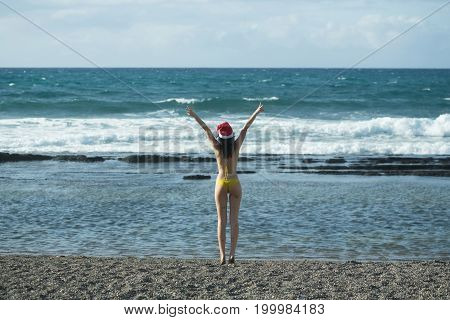 Woman In Santa Claus Hat Rising Hands To Blue Sky