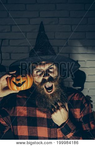 Halloween man shouting with pumpkin in darkness. Scary hipster with beard in witch hat and plaid shirt. Mystery and horror concept. Holiday celebration symbols on brick wall. Jack o lantern.