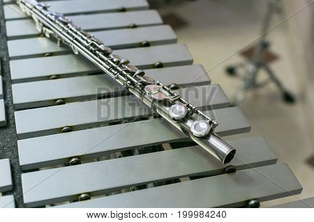 symphonic and brass band, percussion and wind instruments concept - beautiful closeup on shiny western concert flute lies on xylophone, education and orchestra concert, beige bars without mallets