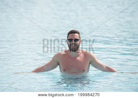 Man with beard and mustache on smiling happy young handsome face in black sunglasses with tanned skin standing waist deep in blue sea water having sun bathing in summer