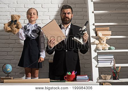 School and fathers day concept. Girl and dad on white brick background. Schoolgirl and man with proud and confused faces hold toy bear book and microscope. Family stands by desk with school supplies