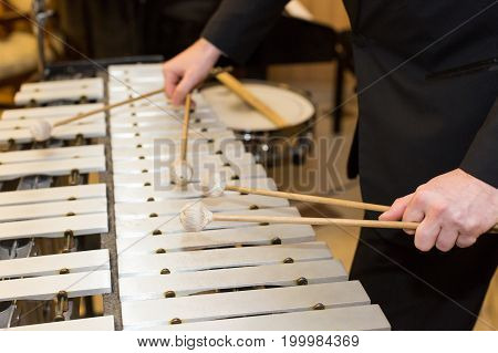xylophone in orchestra, playing percussion instruments concept - closeup on wooden bars with four mallets in human hands, performer in black dress, glockenspiel, art of music, selective focus