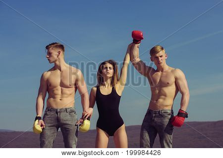 Boxer workout and healthy fitness. Winner and loser in boxing gloves with girl. Woman and twins with muscular body. Men and coach sunny outdoor on blue sky. Sport people or team work.