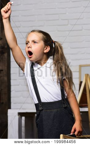 Schoolgirl With Grumpy Face Shouts And Holds Small Chalk
