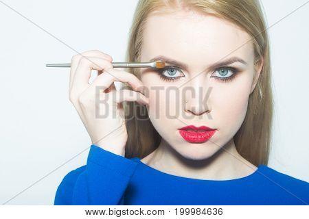 Woman With Blue Eyes Applying Shadows On Eyelids