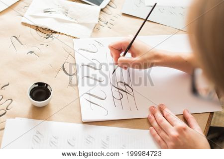 calligraphy, handwriting, technique concept. woman with beautiful elegant hands inscribing capital russian letters carefully in italic type with black ink and thin brush, drawing